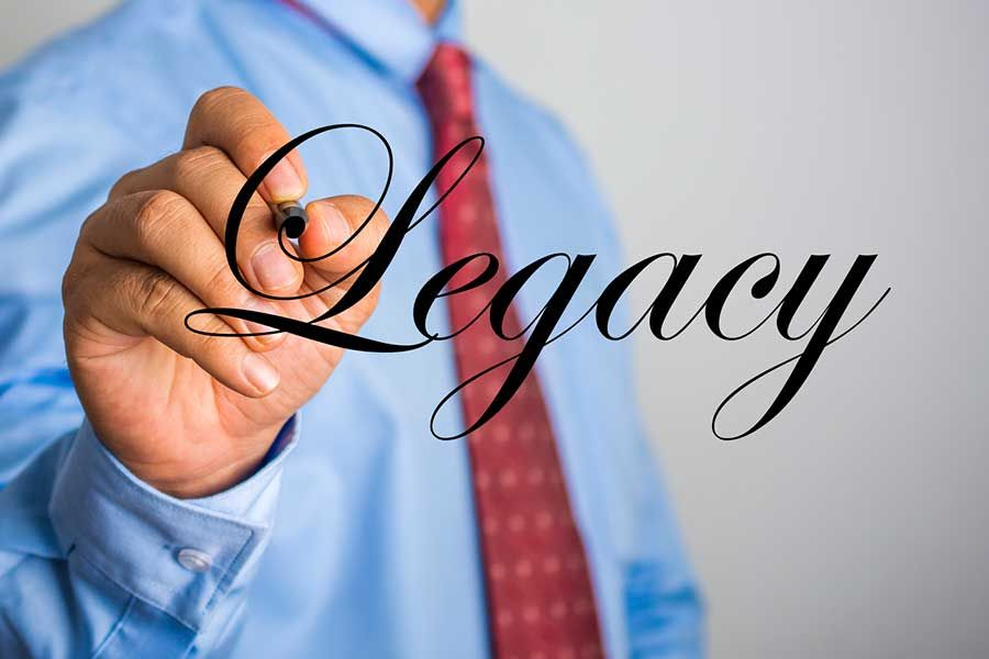 Hand pointing the the word Legacy.