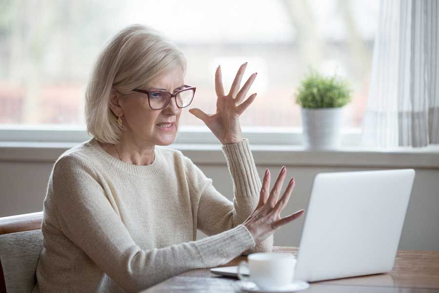 Older Female in Front of Laptop Frustrated by Spam